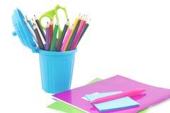 Cuadernos coloridos, pluma y cubo de basura miniatura con el supplie del escritorio Foto de archivo
