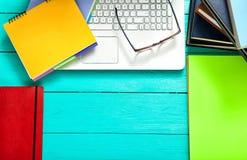 Cuadernos con el espacio de la copia y accesorios coloridos en la tabla de madera azul Visión superior Imágenes de archivo libres de regalías