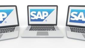 Cuadernos con el logotipo del SE de SAP en la pantalla Representación conceptual del editorial 3D de la informática Foto de archivo libre de regalías