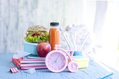 Cuadernos del almuerzo escolar y de la escuela Reloj de alarma rosado Lugar para el texto Niñez feliz Imagen de archivo libre de regalías