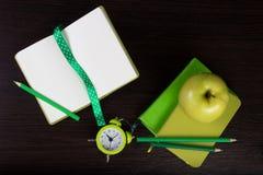 Cuadernos, lápices, reloj y manzana en fondo de madera oscuro Imagen de archivo