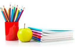 Cuadernos, lápices y manzana. Fotografía de archivo