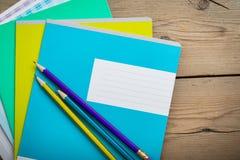 Cuadernos para el schoolon la tabla de madera imagen de archivo libre de regalías