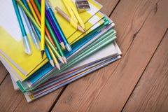 Cuadernos para el schoolon la tabla de madera fotos de archivo