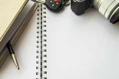 Cuadernos que se sobreponen con llaves de la cámara y del coche imagen de archivo libre de regalías