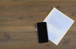 Cuadernos, smartphone en una tabla de madera foto de archivo libre de regalías