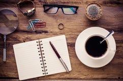 Cuadernos, tazas, vidrios en un escritorio de madera Foto de archivo libre de regalías