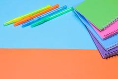 Cuadernos y plumas multicolores papel fuentes de escuela en un fondo azul y anaranjado imagen de archivo libre de regalías