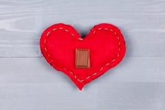 Cuadrado del chocolate con leche en corazón hecho en casa rojo en la madera gris Fotografía de archivo libre de regalías