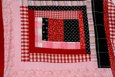 Cuadrado del edredón de la cabaña de madera rojo y rosado Imágenes de archivo libres de regalías