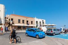Cuadrado en el centro de la ciudad con los coches parqueados y los turistas que caminan Isla de Crete foto de archivo libre de regalías