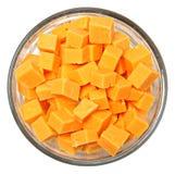 Cuadrados cortados en cuadritos del queso cheddar en cuenco sobre blanco fotos de archivo