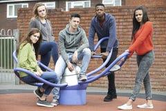 Cuadrilla de adolescentes que cuelgan hacia fuera en el patio de los niños Foto de archivo libre de regalías