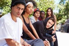 Cuadrilla de gente joven en el ambiente urbano que se sienta en banco Imagen de archivo