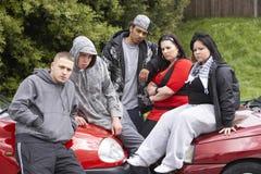 Cuadrilla de juventudes que se sientan en los coches Imágenes de archivo libres de regalías