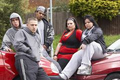 Cuadrilla de juventudes que se sientan en los coches Foto de archivo