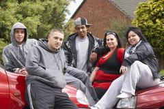 Cuadrilla de juventudes que se sientan en los coches Imagen de archivo libre de regalías