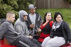 Cuadrilla de juventudes que se sientan en los coches fotos de archivo