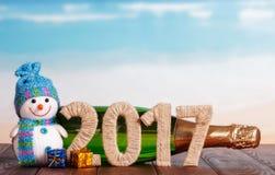 Cuadros 2017, champán de la botella, muñeco de nieve, regalos en la tabla contra el mar Imagenes de archivo
