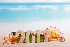 Cuadros 2017, champán de la botella y flores en arena contra el mar Fotos de archivo