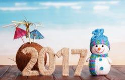 Cuadros coco 2017 y muñeco de nieve en la tabla contra el mar Imagen de archivo libre de regalías