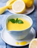 Cuajada de limón en cuenco de cerámica con los limones frescos en un fondo azul de la servilleta Foco selectivo Fotos de archivo