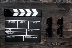 Cualidades del director de cine Clapperboard y gafas de sol de la película en la opinión superior del fondo de madera de la tabla Imagen de archivo libre de regalías