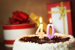 Cuarenta años de cumpleaños Torta con las velas y los regalos ardientes Imagen de archivo