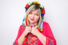 Cuarenta años de señora que lleva en vestido rojo con la guirnalda de flores Imagen de archivo libre de regalías