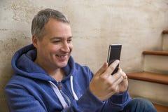 Cuarenta años del asiento del hombre de negocios en las escaleras dentro del edificio de oficinas que mira en un teléfono móvil Foto de archivo libre de regalías