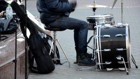 Cuarenta atractivos algo hombre juega los tambores en una banda, afuera en una calle, en una etapa del gazebo metrajes