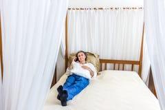 Cuarenta en el teléfono en cama de la cama imperial Fotos de archivo