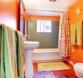 Cuarto de baño anaranjado y verde con el suelo de la tina y de madera. Foto de archivo
