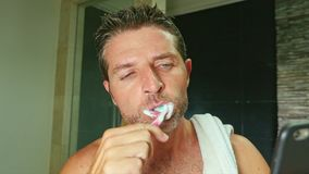 Cuarto de baño atractivo del hombre del adicto a Internet en casa con la toalla en los dientes que se lavan del hombro con el cep metrajes