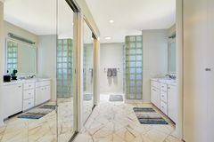 Cuarto de baño blanco con las puertas de la diapositiva del espejo Fotografía de archivo libre de regalías