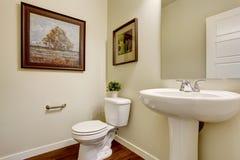 Cuarto de baño brillante con el soporte y el retrete blancos del lavabo Foto de archivo