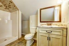 Cuarto de baño con el techo saltado Gabinete y espejo de la vanidad Foto de archivo