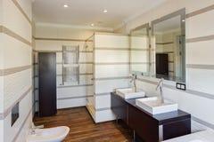 Cuarto de baño con la pared rayada y el fregadero de cerámica dos imagenes de archivo