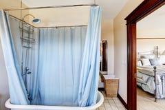 Cuarto de baño con la tina de baño y la cortina azul alrededor de ella Imagenes de archivo