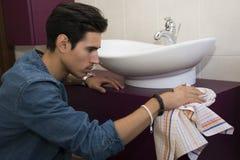 Cuarto de baño de la limpieza del hombre joven que limpia el lavabo y los gabinetes Foto de archivo