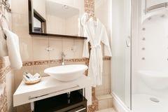 Cuarto de baño dentro de cuartos de un apartamento o de un hotel Limpie la toalla y la albornoz blancas en una suspensión prepara imagen de archivo libre de regalías