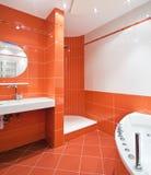 Cuarto de baño en colores anaranjados y blancos imagen de archivo