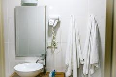 Cuarto de baño en el hotel con todos los accesorios necesarios del cuarto de baño para el turista Foto de archivo