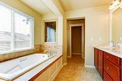 Cuarto de baño en marfil suave con el gabinete brillante Imágenes de archivo libres de regalías