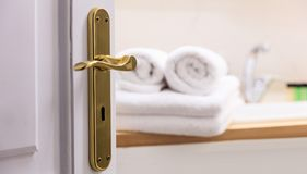 Cuarto de baño de la puerta abierta Empañe las toallas blancas rodadas y dobladas al lado del fregadero Detalles de la puerta Foto de archivo libre de regalías