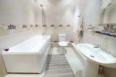 Cuarto de baño limpio y nuevo con el retrete con las tejas en las paredes Imágenes de archivo libres de regalías