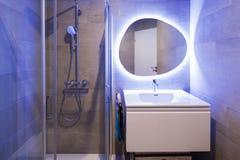 Cuarto de baño de mármol moderno con el espejo retroiluminado foto de archivo libre de regalías
