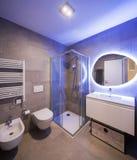 Cuarto de baño de mármol moderno con el espejo retroiluminado imagen de archivo
