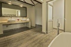 Cuarto de baño moderno con dos lavabos y un baño Foto de archivo libre de regalías