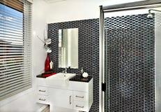 Cuarto de baño moderno con paredes bien adornadas y una encimera en a Foto de archivo